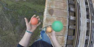 Jonglerie la mare inaltime: executa un numar cu trei mingi in timp ce traverseaza un viaduct pe balustrada lui